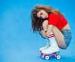 Beautiful brunette with long hair in a red top and denim shorts posing sitting on her haunches in roller derby skates and white spats on the ramp skate park