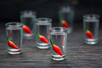 selectiv focus glasses of cold vodka with peppers  on wooden tab