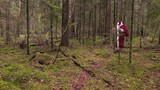 Santa Claus with gift bag walking through the forest