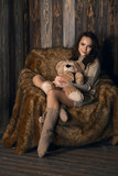 Cute girl in knee socks and sweater with Teddy bear in her hands