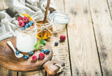 Glass jar of white yogurt with fresh garden berries, peach and honey on serving board over rustic wooden background, copy space, selective focus, horizontal composition