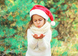 Christmas child little girl in santa red hat blowing snow lying