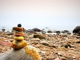 Balanced stone pyramid on sea shore, waves in background. Colorful flat stones