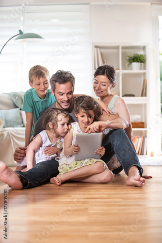Fotografiet At home, a family sitting on wooden floor while using a tablet
