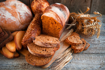 Assortment of fresh baked bread on wooden table background