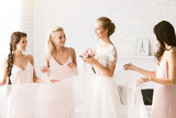 Smiling bridesmaids holding the dress of the bride