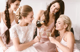 Amused bride and bridesmaids having hen party at home