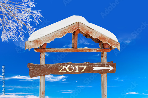 2017 written on a wooden direction sign, blue sky and frozen tree background