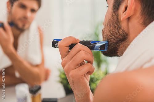 Poster Confident guy shaving in bathroom