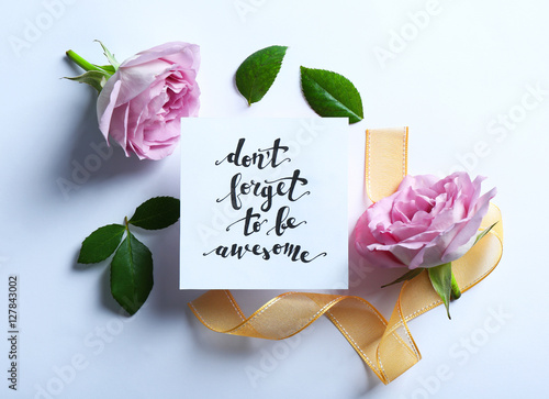 "Poster Inscription ""DON'T FORGET TO BE AWESOME"" written on paper with flowers and ribbo"