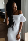 Adorable pretty woman with black skin standing near the table. Girls is wearing elegant white dress with sexy bare shoulders. She looking at the window and put her hand on hair.