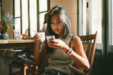 Young beautiful asian female is drinking coffee and reading the morning news by the mobile phone internet connection while sitting in a cozy coffee shop in the morning.