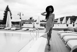 Black and white photo of charming, touching, tender, beautiful woman with dark skin wearing dress in stripes and hat. Model walking on the teritory near pool of vip hotel. Windy weather. Cold.