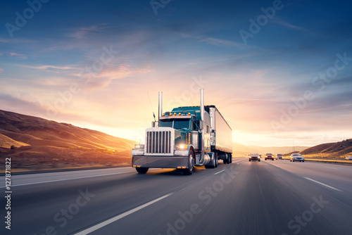 American style truck on freeway pulling load. Transportation the