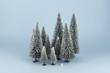 Bodegón mininalista de bosque en invierno con un diminuto muñeco de nieve. Fondo azul.