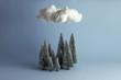 Bodegón mininalista de bosque en invierno sobre el que flota una nube. Fondo azul con sombras.