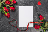 Sheet of paper, pen, hearts, ribbon and red roses on black table. Valentines Day background.