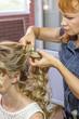 Stylist makes wedding hairstyle.