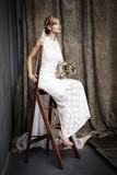 Stunning bride in white on ladder in studio