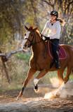 Young girl riding a horse - 127900401