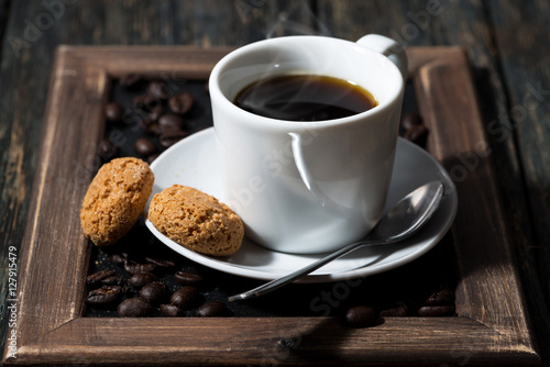 Poster cup of black coffee and cookies on a tray