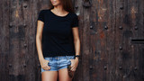 A cropped photo of a young woman wearing black blank t-shirt and blue jeans shorts standing on the wooden door background. Empty space for text or design.