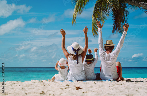 Poster happy family with two kids hands up on the beach