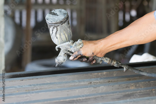 Poster Male holding spray gun and painted steel