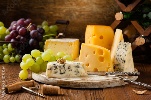 Mix cheese on wooden board. Poster