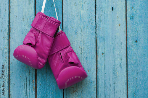 Pink boxing gloves on blue cracked wooden background