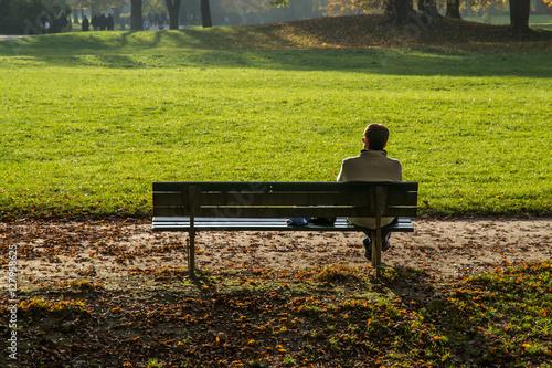 Poster Persona da sola su una panchina nel parco