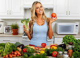 Woman with broccoli and tomato in the kitchen.