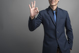 Close up of businessman in blue suit hand ok on gray background
