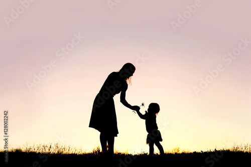 Silhouette of Baby Girl Giving Mom Flower at Sunset Poster