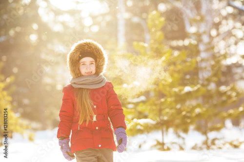Poster Little girl in red jacket walks in wood in winter (sunshine)