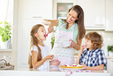 Mother and children baking cake together