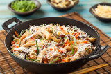 Fototapety Rice noodles with chicken, mushrooms mun and vegetables in wook.