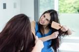 Unsmiling brunette combing