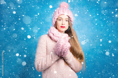 Winter portrait of a sad woman in knitted pink scurf, gloves and hat on the blue Poster