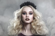 Beauty portrait of a beautiful young blonde woman with gothic make-up and decorative wreath in a puff of smoke.