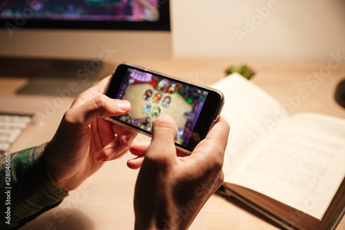 Man hands playing videogames on cell phone in the evening