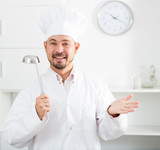 Positive young cook holding soup ladle