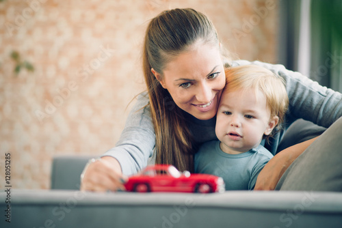 Mom and her toddler son plays with red car in their cosy living room