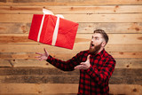 Young bearded man trying to catch gift box in motion