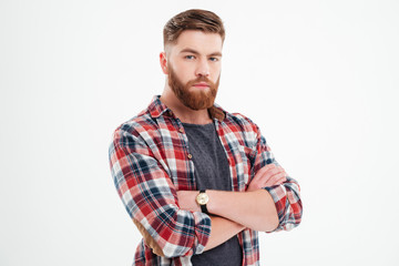Satisfied bearded man in plaid shirt with arms folded