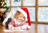 Happy girl in a red Christmas hat writing a letter to Santa Claus