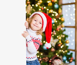 Little girl in red santa hat behind white board. Space for text