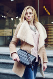 Fototapety Outdoor portrait of young beautiful fashionable woman posing on street. Model wearing stylish winter fake fur coat, holding small black quilted bag. Lady looking aside. Waist up. Toned