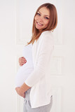 Soft look of woman expecting a baby looking at the camera isolat