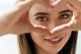 Fototapety Beautiful Happy Woman Showing Love Sign Near Eyes.
